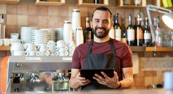 man with tablet behind counter