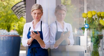waitress looking at her phone outside a restaurant